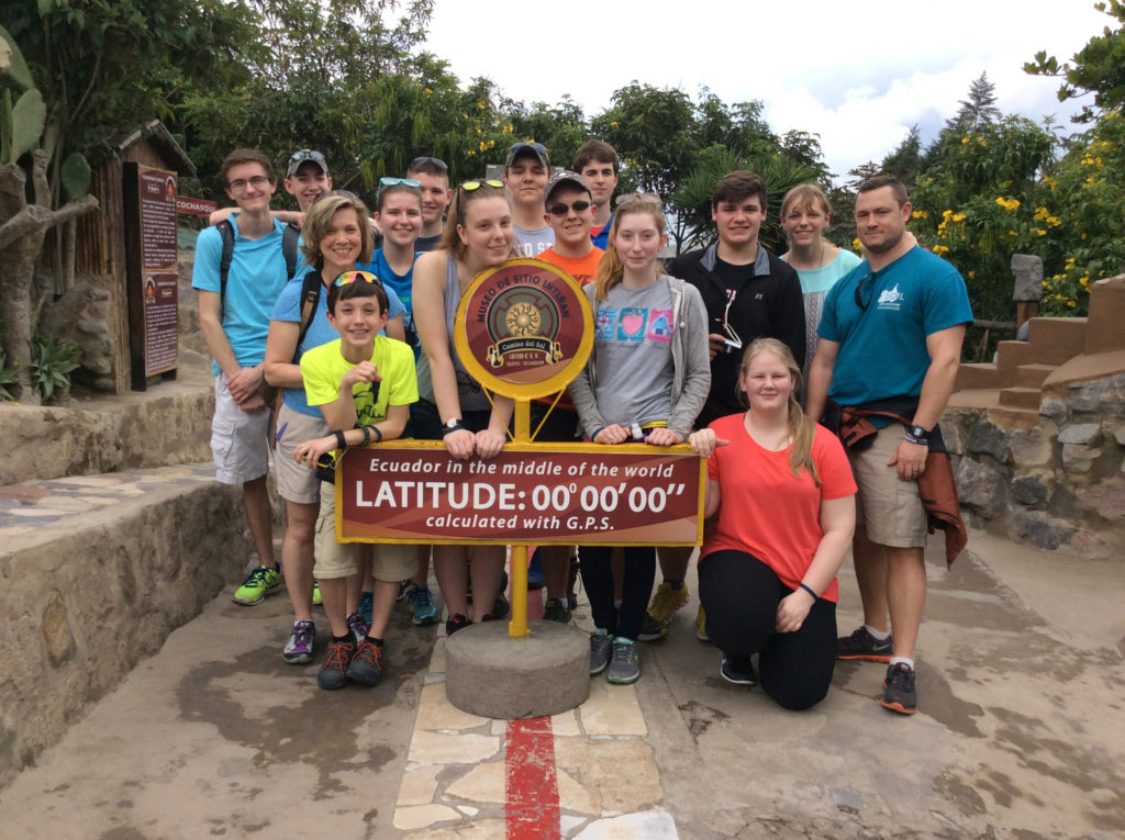 Group poses together by an Ecuador sign