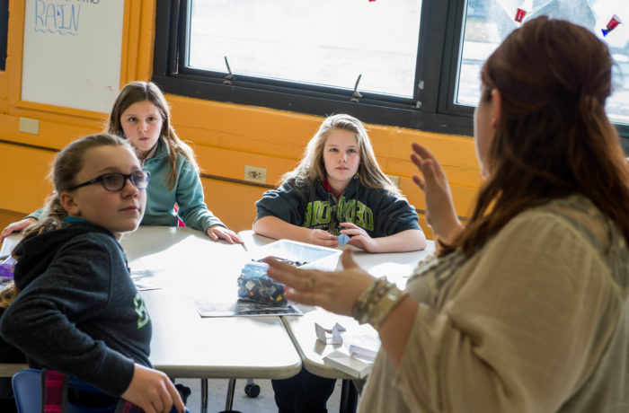 Three female students listen to instructor