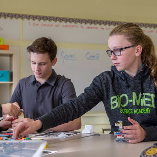 Female and male student work together with legos